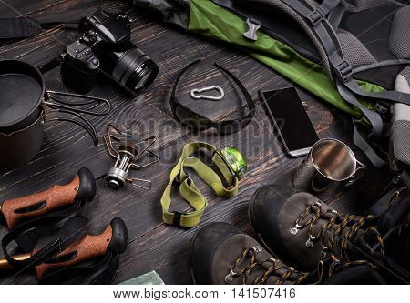 Hiking accessories set on dark wooden background:  boots, backpack, sunglasses, photo camera, map, smartphone, flashlight and others. Top view