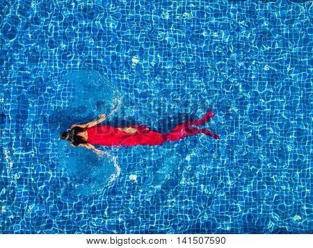 woman in swimming pool in red dress
