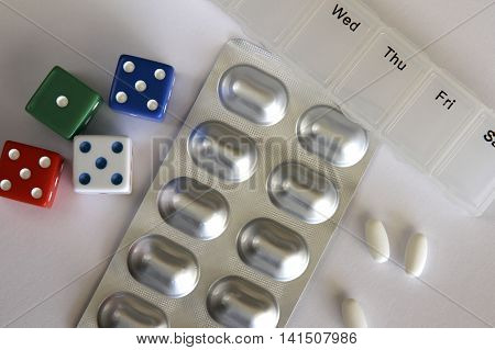 Some white pills, pill box and dice.