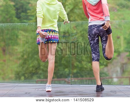 Two fit young women friends exercising in a park. Active healthy lifestyle and outdoor workout concept