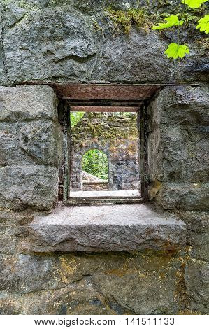 Looking through the window of abandoned stone castle house at Wildwood Trail in Forest Park Portland Oregon