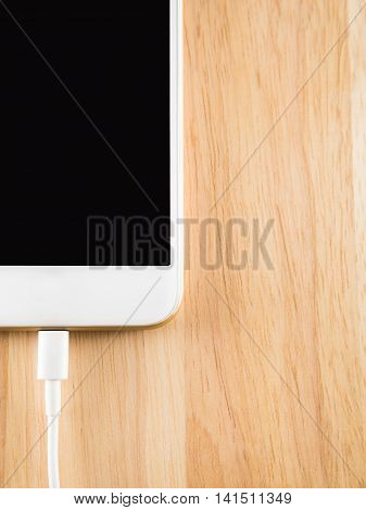 Top view (Flat Lay) of smart phone charging with USB cable on wooden texture background Copy space Vertical poster
