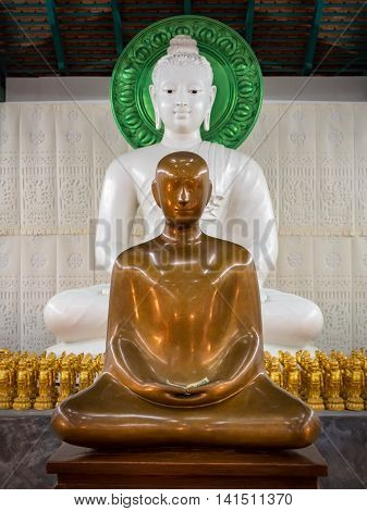 Beautiful gold meditation monk statue in front of white meditation Buddha statue and many golden baby Buddha statue
