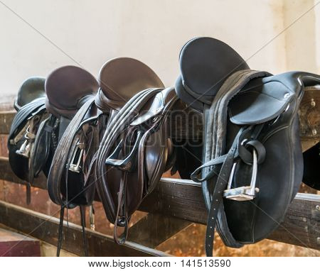 Rider Leather Saddles on fence cowboy rope leather