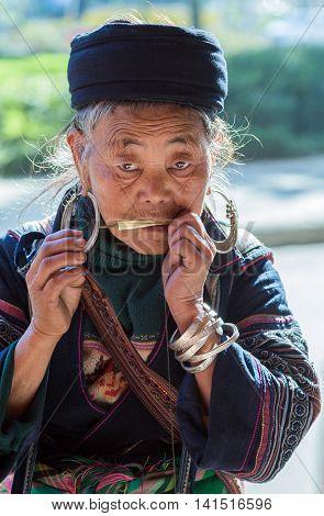 Sapa Lao Cai Province Vietnam - November 25 2014: Hmong old woman at a dan moi and wearing traditional attire in Sapa town on November 25 2014 Lao Cai Province North Vietnam.