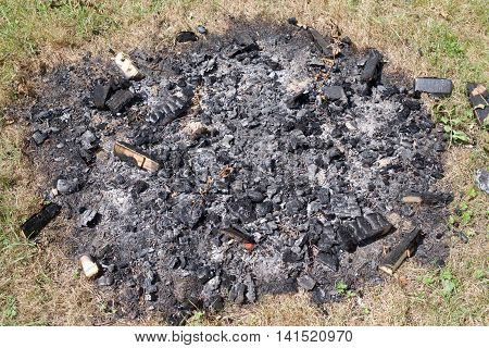 embers and ashes of a fire picnic out in the countryside