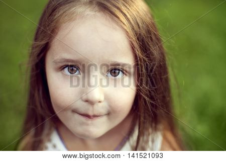beautiful white girl with long hair and hazel big eyes looking straight at the camera and smiling in summer outdoors close-up