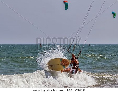 MUI NE VIETNAM - FEBRUARY 15 2015: Surfer at Kiteboard jumping from wave and Surf Fun in the Ocean Extreme Sport.