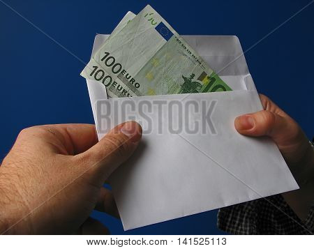 Hand with money in the white envelope