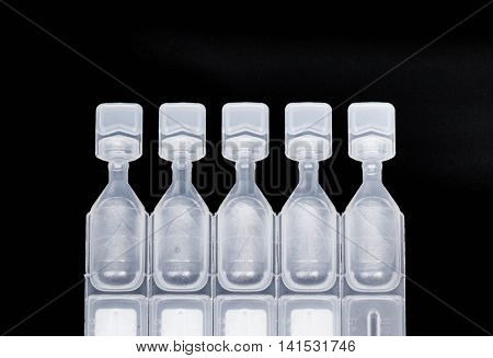 Lubricant eye drops vials on black background