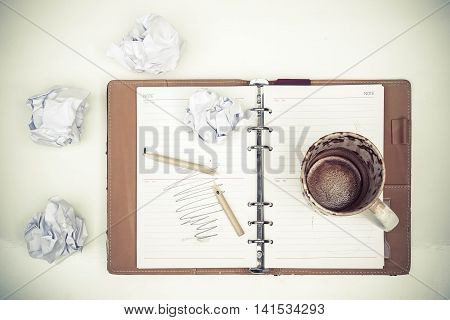 A cup of empty coffee on a notebook with scrap papers and broken pencil / Felling frustrated because no ideas coming up concept