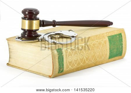 Wooden gavel, handcuffs and big book of law