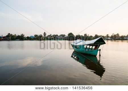 A wooden boat in the middle of the Sarawak River, Sarawak, Malaysia.
