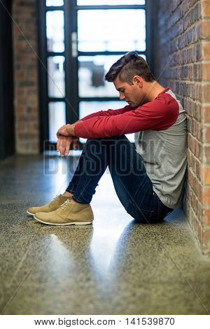 Side view of stressed man sitting in corridor