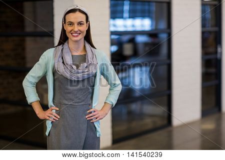Portrait of smiling businesswoman standing in creative office
