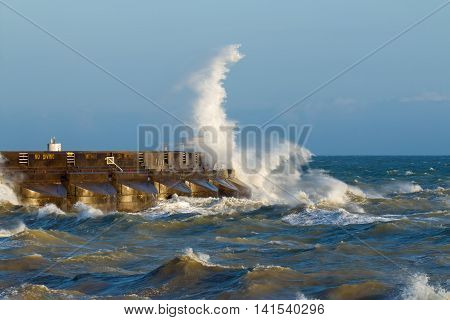 Waves breaking over the east arm of Brighton Marina on the South Coast of England during windy weather and high seas in the English Channel.