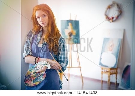 Thoughtful attractive young woman painter with long red hair in apron holding art palette and brush in artist workshop