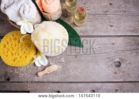 Spa setting. Sea salt towels bottles with aroma oil and wisps on vintage wooden background. Selective focus. Place for text.