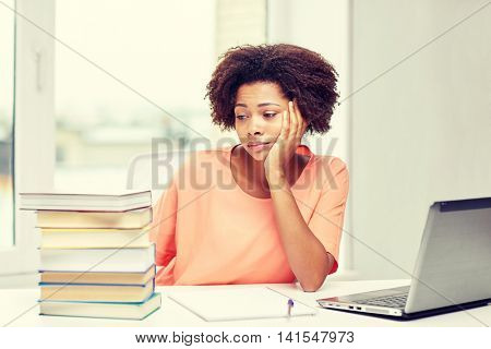 people, technology and education concept - bored african american young woman sitting at table with laptop computer, books and notepad at home
