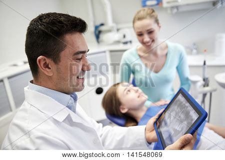 people, medicine, stomatology, technology and health care concept - happy male dentist looking at teeth x-ray on tablet pc computer and patient girl with her mother at dental clinic office