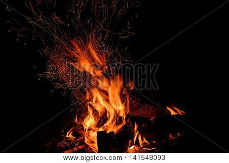 Red and orange spurts of flames charcoal firewood in the fire and sparks in the form of tracks on a black background poster