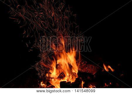 Red and orange spurts of flames charcoal firewood in the fire and sparks in the form of tracks on a black background