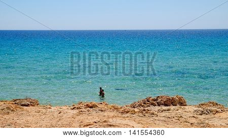View on the bue sea and two persons swimming in Pinus Village. 02.08.2016, Sardinia.