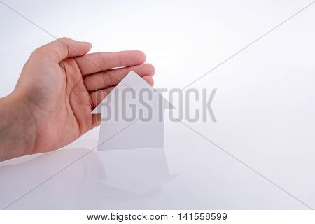 Hand holding a paper house on a white background