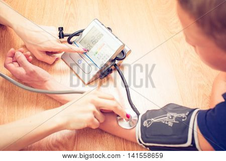Beautiful young female doctor is checking the blood pressure of the patient.