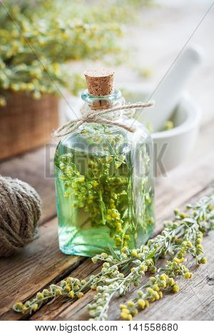 Bottle of absent or tincture of tarragon healthy herbs absinthe healing herbs and mortar on table. Herbal medicine.