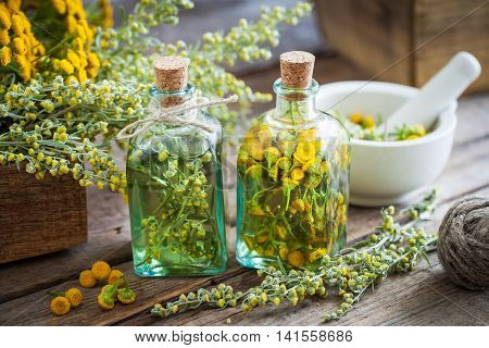 Tincture bottles of tansy and tarragon healthy herbs absinthe healing herbs in wooden box and in mortar. Herbal medicine.