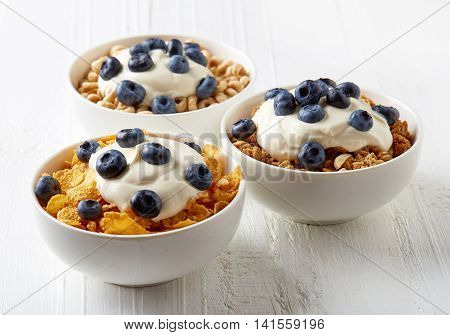 Three Types Of Cereals With Yogurt And Blueberries On White Table