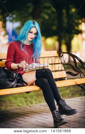 Pretty young blue-haired rock girl sitting on bench in square and reading a book