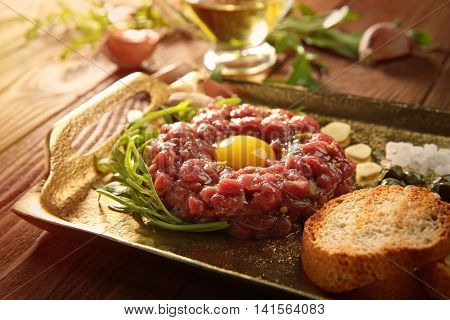 Steak tartar with chopped onion and pickles on a tray