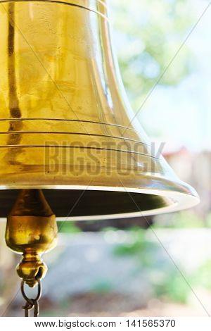 close up image of golden bell in railway station