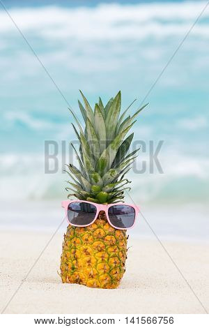 Pineapple Fruit In Sunglasses On Sand Against Turquoise Caribbean Sea Water