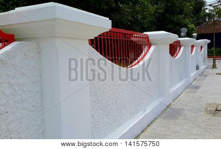 white stucco wall with flared posts, red wrought iron grill fence on top, fitting into the curved parts of the wall, Songkhla museum, Thailand