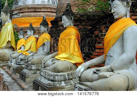 Ayutthaya Thailand - December 28 2005: A row of seated Buddhas draped with orange and saffron silk sashes at Wat Yai Chai Mongkon