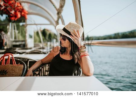 Woman in hat enjoying beautiful day on the lake