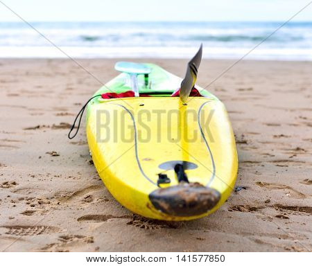Multicolored canoe on the beach. Selective focus of a yellow and green canoe boat and view to the turquoise sea and blue sky. Focus on the foreground and copy space.