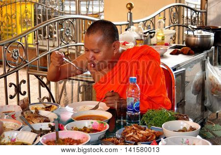 Bangkok Thailand - January 10 2013: Buddhist Monk in an orange robe eating a sumptuous lunch on an outdoor terrace at Wat Hua Lamphong