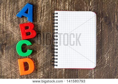 ABCD spelling from plastic letters and blank notebook on wooden background