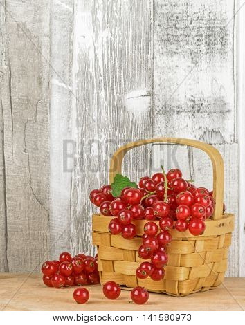 Red currants in a basket with a wooden background