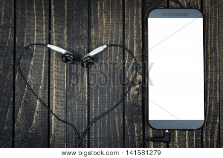 Love music concept with phone and heart shape earphones on wooden table