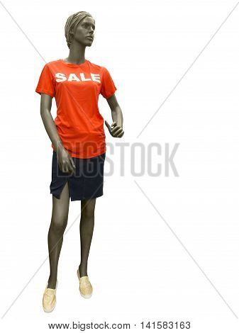 Female mannequin dressed in skirt and red t-shirt on which sale is written. No brand names or copyright objects.