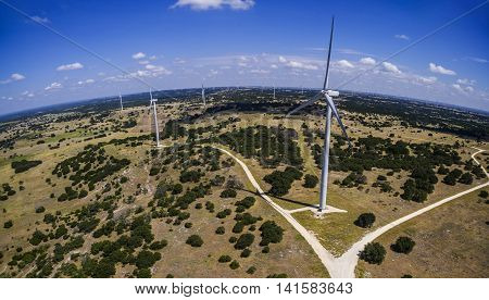 Aerial View Over Wind Turbine Farm Panoramic angle near many Turbines creating green renewable energy for the future