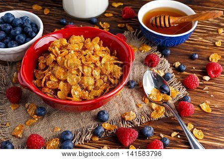 Corn Flakes with berries raspberries, blueberries, glass of milk, and sweet honey