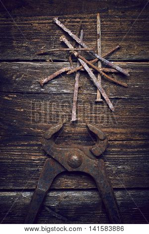 old rusty tongs with nails on wooden boards background