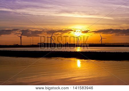 Wind turbines near seashore at sunset - ecology concept