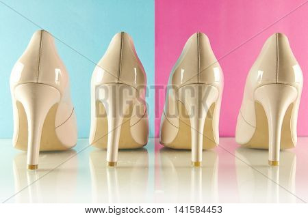 Woman's high heel shoes on blue and pink background